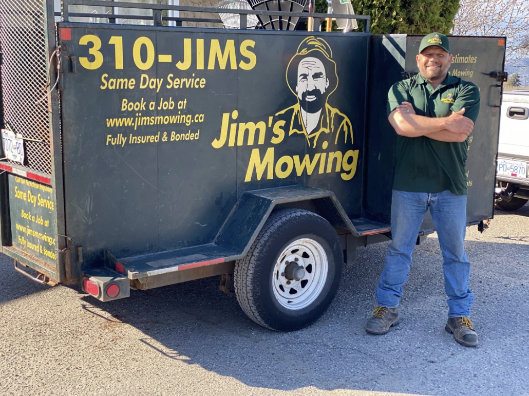 Cory Rewuski our Jim's Mowing franchisee in Kelowna in front of trailer