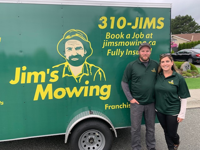 Steve and Gillian Campbell our Jim's Mowing franchisee in Nanaimo, South Parksville and Nanoose in front of trailer